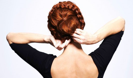 Studio shot of a redhead woman with a braided up-do posing against a gray background